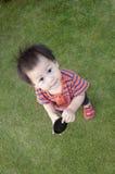 Ein jähriger Junge, der auf Gras steht Stockfoto