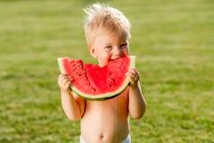 Ein jähriges Baby, das Wassermelone im Garten isst lizenzfreie stockbilder