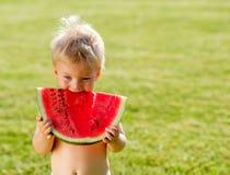 Ein jähriges Baby, das Wassermelone im Garten isst lizenzfreie stockfotografie