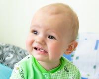 Ein jähriges Baby war umgekippt und Schreien Kleiner Junge in einer hellgrünen Klage mit Schafen lizenzfreie stockfotos