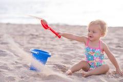 Ein jähriges Mädchen, das im Sand spielt Stockbilder