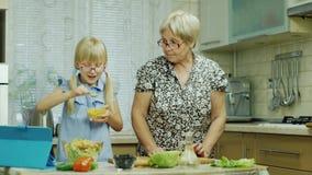 Ein 6-jähriges Mädchen in den rosa Gläsern bereitet einen Salat in der Küche zu Ihre Großmutterhilfen, benutzen eine Tablette stock video footage