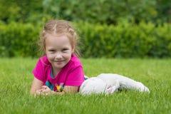 Ein 4-Jahr-altes Mädchen, das mit einem knuddeligen Spielzeug auf dem Gras in einem Park spielt Lizenzfreie Stockfotografie