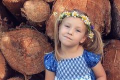 Ein 3-Jahr-altes Mädchen mit Kamillenkranz steht vor einem hölzernen Stapel Lizenzfreies Stockbild