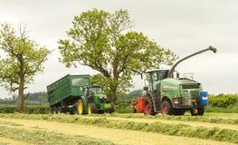 Ein John Deere-Traktor mit forager Fendt Katana 65 Lizenzfreie Stockbilder