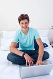 Ein Jugendkerl, der einen Laptop in seinem Schlafzimmer verwendet Stockbilder