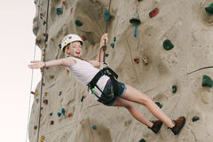 Ein jugendlich Mädchen, das auf einer Felsenwand zurück sich lehnt an der Überrollschutzvorrichtung klettert stockfotografie