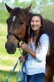Ein jugendlich Mädchen lacht mit ihrem Pferd Stockfotografie