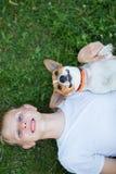 Ein Jugendlicher, der mit einem Hund in der Natur spielt stockbild