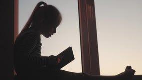 Ein Jugendlicher des kleinen Mädchens, der Geschichte mit Buch am offenen Fenster auf Schwelle auf Sonnenunterganghintergrund sic stock video footage