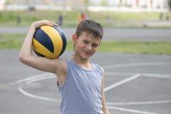 Ein Jugendlicher in einer Weste hält einen Ball in seiner Hand lizenzfreies stockfoto