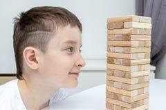 Ein jugendlicher kaukasischer Junge, der Holzklotzturm-Brettspiel f?r das ?ben seiner k?rperlichen und Geistesf?higkeit und Unter lizenzfreie stockfotos