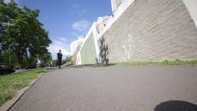 Ein Jugendlicher reitet ein Skateboard auf den Bürgersteig unter einem Wohnblock stock video