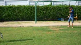 Ein Jugendlichjunge und -mädchen spielen Badminton auf einem grünen Rasen im Hinterhof ihres Hauses stock video footage