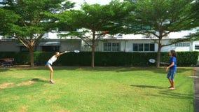 Ein Jugendlichjunge und -mädchen spielen Badminton auf einem grünen Rasen im Hinterhof ihres Hauses stock video