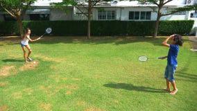 Ein Jugendlichjunge und -mädchen spielen Badminton auf einem grünen Rasen im Hinterhof ihres Hauses stock footage