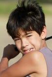 Ein Junge 10 installierte, um einen Golfball am Strand zu schlagen Stockfotografie