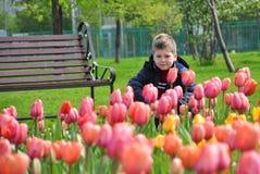 Ein Junge auf einer Parkbank Lizenzfreie Stockfotos