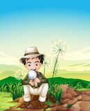 Ein Junge, der über einem Stumpf hält eine Vergrößerungslinse sitzt Stockbild