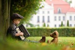 Ein Junge, der Akkordeon spielt lizenzfreie stockbilder