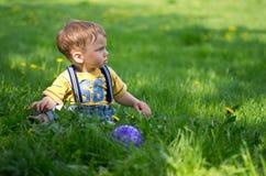 Ein Junge, der auf dem Gras mit einer Kugel sitzt Stockfotos