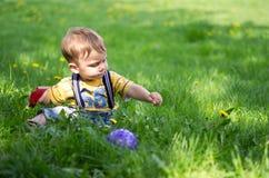 Ein Junge, der auf dem Gras spielt Lizenzfreies Stockfoto