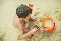 Ein Junge, der auf dem Strand mit Sand spielt Lizenzfreies Stockbild