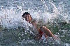 Ein Junge, der auf einer großen Welle spritzt Stockfotografie