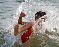 Ein Junge, der auf einer Welle spritzt Stockfotografie