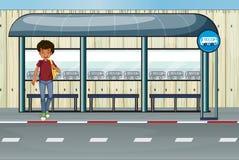 Ein Junge an der Bushaltestelle Lizenzfreie Stockbilder