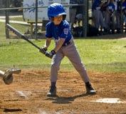 Ein Junge, der damit die Kugel die Platte überwacht, kreuzt. stockfoto
