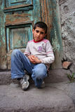 Ein Junge, der an der Türstufe sitzt Stockbild