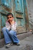 Ein Junge, der an der Türstufe sitzt Stockfotografie