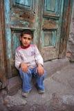 Ein Junge, der an der Türstufe sitzt Lizenzfreies Stockfoto