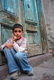 Ein Junge, der an der Türstufe und am Denken sitzt Lizenzfreie Stockfotos