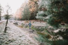 Ein Junge, der die Flussbank bereitsteht Russland, UralJanuary, Temperatur -33C Winterwald auf dem Fluss lizenzfreies stockfoto