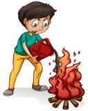 Ein Junge, der ein Lagerfeuer macht Lizenzfreies Stockbild