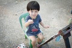 Ein Junge, der eine Farbbürste anhebt Lizenzfreie Stockfotografie