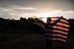 Ein Junge, der eine große amerikanische Flagge, Unabhängigkeitstag hält Stockbilder