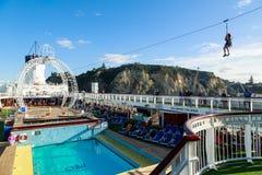 Ein Junge, der eine Ziplinie Hoch über der Poolplattform eines Kreuzfahrtschiffs reitet stockbild