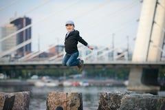 Ein Junge, der an einem Pier springt Lizenzfreie Stockbilder