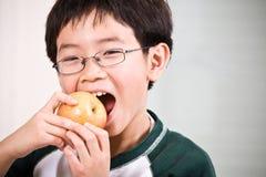 Ein Junge, der einen Apfel isst Lizenzfreie Stockfotos