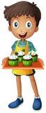 Ein Junge, der einen Behälter mit kleinen Kuchen hält Stockfotografie