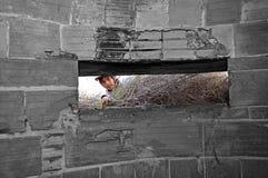 Ein Junge, der einen Bunker des Zweiten Weltkrieges untersucht Stockfoto