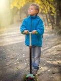Ein Junge, der einen Roller im Herbstpark reitet stockfoto