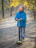 Ein Junge, der einen Roller im Herbstpark reitet lizenzfreie stockfotos