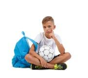 Ein Junge, der im Lotussitz sitzt Ein sportives Kind mit heller Schultasche und Fußball lokalisiert auf einem weißen Hintergrund Stockfotografie