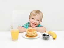 Ein Junge, der mit seinem Frühstück von Pfannkuchen, Beeren, Verbot lächelt Lizenzfreie Stockbilder
