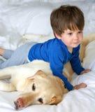 Ein Junge, der mit seinem Hund ringt Lizenzfreies Stockfoto