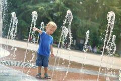 Ein Junge, der mit Wasser im Parkbrunnen spielt Hei?er Sommer stockbild